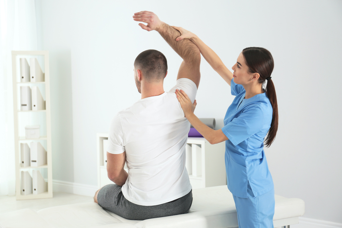 Doctor working with patient in hospital. Rehabilitation physiotherapy